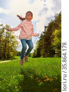 Glückliches Mädchen beim Seil springen auf einer Wiese im Sommer ... Стоковое фото, фотограф Zoonar.com/Robert Kneschke / age Fotostock / Фотобанк Лори