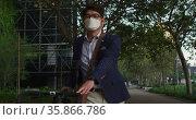 Asian man wearing face mask with bicycle walking on the street. Стоковое видео, агентство Wavebreak Media / Фотобанк Лори