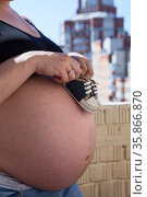 Small baby shoes in female hands and large belly, pregnancy concept. Стоковое фото, фотограф Кекяляйнен Андрей / Фотобанк Лори