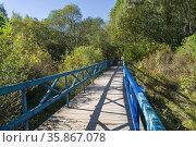 A wooden pedestrian bridge in a small ravine. Early autumn, sunny... Стоковое фото, фотограф Zoonar.com/Sergey Rybin / age Fotostock / Фотобанк Лори