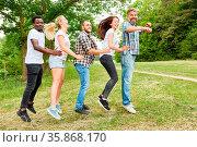 Glückliche multikulturelle Gruppe beim Hüpfen auf einer Wiese beim... Стоковое фото, фотограф Zoonar.com/Robert Kneschke / age Fotostock / Фотобанк Лори