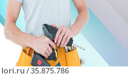 Midsection of handy man holding drill on blue and white stripes. Стоковое фото, агентство Wavebreak Media / Фотобанк Лори