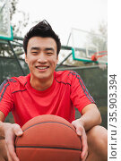 Young man sitting with a basketball on the basketball court, portrait  . Стоковое фото, агентство Ingram Publishing / Фотобанк Лори