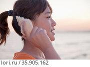 Teenage girl listening to seashell, profile. Стоковое фото, агентство Ingram Publishing / Фотобанк Лори