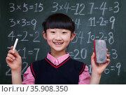 Portrait of schoolgirl in front of blackboard holding chalk and eraser. Стоковое фото, агентство Ingram Publishing / Фотобанк Лори