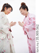 Two young smiling  woman in Japanese kimonos bowing to each other, studio shot. Стоковое фото, агентство Ingram Publishing / Фотобанк Лори