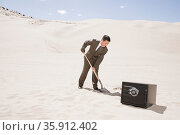 Man digging by safe in desert. Стоковое фото, фотограф Shannon Fagan / Ingram Publishing / Фотобанк Лори