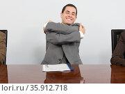 Businessman hugging himself. Стоковое фото, фотограф Shannon Fagan / Ingram Publishing / Фотобанк Лори