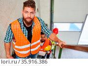 Junger Mann als Handwerker oder Bauarbeiter in der Ausbildung mit... Стоковое фото, фотограф Zoonar.com/Robert Kneschke / age Fotostock / Фотобанк Лори