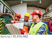 Gruppe Bauarbeiter mit Bauzeichnung bei der Planung einer Fabrik ... Стоковое фото, фотограф Zoonar.com/Robert Kneschke / age Fotostock / Фотобанк Лори