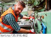 Lächelnder Arbeiter in der Metallfabrik bedient Standbohrmaschine... Стоковое фото, фотограф Zoonar.com/Robert Kneschke / age Fotostock / Фотобанк Лори