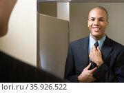 Man adjusting tie in mirror. Стоковое фото, фотограф Shannon Fagan / Ingram Publishing / Фотобанк Лори