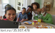 African american girl taking a selfie while having breakfast with her family at home. Стоковое видео, агентство Wavebreak Media / Фотобанк Лори