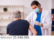 Old man visiting young doctor in covid-19 vaccination concept. Стоковое фото, фотограф Elnur / Фотобанк Лори