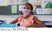 Portrait of mixed race schoolgirl wearing face mask, sitting in classroom looking at camera. Стоковое видео, агентство Wavebreak Media / Фотобанк Лори