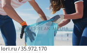 Two diverse female friends putting rubbish in refuse sacks at the beach. Стоковое видео, агентство Wavebreak Media / Фотобанк Лори