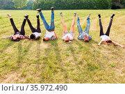 Junge Leute liegen auf einer Wiese und strecken die Beine beim Teambuilding... Стоковое фото, фотограф Zoonar.com/Robert Kneschke / age Fotostock / Фотобанк Лори