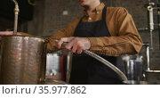 Caucasian man working at gin distillery, wearing apron, connecting pipe to distillation equipment. Стоковое видео, агентство Wavebreak Media / Фотобанк Лори