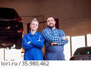 Confident young mechanics man and woman at garage. Mechanics standing... Стоковое фото, фотограф Zoonar.com/Oksana Shufrych / easy Fotostock / Фотобанк Лори