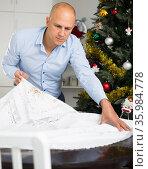 Man spreading tablecloth on table. Стоковое фото, фотограф Яков Филимонов / Фотобанк Лори