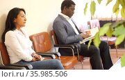 Focused adult hispanic woman wearing white blouse and jeans sitting on chair in office corridor, waiting for job interview. Стоковое видео, видеограф Яков Филимонов / Фотобанк Лори