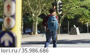 African american man in city, carrying backpack crossing street. Стоковое видео, агентство Wavebreak Media / Фотобанк Лори