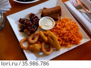 Cheese sticks, chips, croutons and chicken legs with sauce on plate. Стоковое фото, фотограф Яков Филимонов / Фотобанк Лори