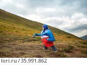 Funny kid in multi-colored big size windcheater walks on the mountain... Стоковое фото, фотограф Zoonar.com/Andrey Bezuglov / easy Fotostock / Фотобанк Лори