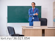 Young male teacher in suit in front of green board. Стоковое фото, фотограф Elnur / Фотобанк Лори