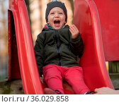 Happy baby boy with a cap laughing loudly sitting on a children slide... Стоковое фото, фотограф Zoonar.com/Roberto Binetti Photographer / age Fotostock / Фотобанк Лори