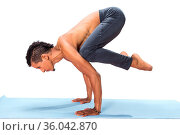 Young man doing yoga asana poses exercise studio photo isolated on... Стоковое фото, фотограф Zoonar.com/Svetlana Radayeva / easy Fotostock / Фотобанк Лори