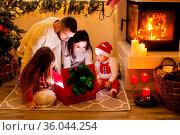 Happy family open Christmas lighting gift box near Christmas tree... Стоковое фото, фотограф Zoonar.com/Oksana Shufrych / easy Fotostock / Фотобанк Лори