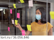 Caucasian businesswoman wearing face mask brainstorming, reading colourful memo notes on glass wall. Стоковое фото, агентство Wavebreak Media / Фотобанк Лори