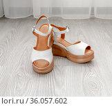 White women's leather sandals stand on the floor in the room. Стоковое фото, фотограф Володина Ольга / Фотобанк Лори