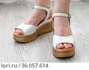 Female feet with White leather sandals stand on floor in the room. Стоковое фото, фотограф Володина Ольга / Фотобанк Лори