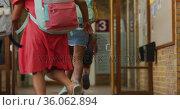 Diverse group of schoolchildren wearing backpacks, running fast through school corridor. Стоковое видео, агентство Wavebreak Media / Фотобанк Лори