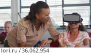 Diverse female teacher standing near happy schoolgirl wearing virtual reality glasses. Стоковое видео, агентство Wavebreak Media / Фотобанк Лори