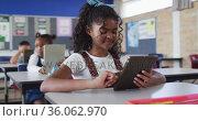 Portrait of happy mixed race schoolgirl sitting at classroom, using tablet, looking at camera. Стоковое видео, агентство Wavebreak Media / Фотобанк Лори