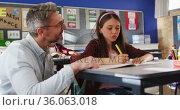 Diverse happy male teacher helping schoolgirl sitting in classroom during learning. Стоковое видео, агентство Wavebreak Media / Фотобанк Лори
