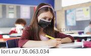 Portrait of caucasian schoolgirl wearing face mask in classroom looking at camera. Стоковое видео, агентство Wavebreak Media / Фотобанк Лори