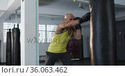 Caucasian male trainer wearing boxing gloves training with punching bag at the gym. Стоковое видео, агентство Wavebreak Media / Фотобанк Лори