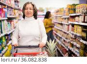 Pensive female shopping at store, walking among shelves and choosing products. Стоковое фото, фотограф Яков Филимонов / Фотобанк Лори