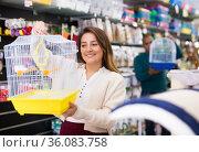 Positive woman buying bird cage at pet store. Стоковое фото, фотограф Яков Филимонов / Фотобанк Лори