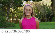 Portrait of happy caucasian girl standing in garden smiling to camera. Стоковое видео, агентство Wavebreak Media / Фотобанк Лори