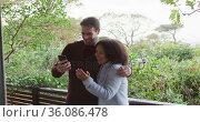 Happy diverse couple looking at smartphone and talking, standing on balcony in the countryside. Стоковое видео, агентство Wavebreak Media / Фотобанк Лори