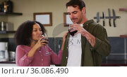 Happy diverse couple standing in kitchen, drinking red wine and embracing. Стоковое видео, агентство Wavebreak Media / Фотобанк Лори