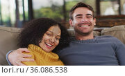 Portrait of happy diverse couple sitting on couch in living room, embracing and smiling. Стоковое видео, агентство Wavebreak Media / Фотобанк Лори