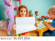 Portrait of beautiful curly girl sitting, holding large sheet of paper... Стоковое фото, фотограф Zoonar.com/OKSANA SHUFRYCH / easy Fotostock / Фотобанк Лори