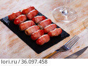 Rolled bacon with sausages on black dish. Стоковое фото, фотограф Яков Филимонов / Фотобанк Лори