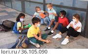 Group of preteen children in face masks resting outdoors in schoolyard during break in lessons. Back school concept during pandemic. Стоковое видео, видеограф Яков Филимонов / Фотобанк Лори